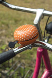 Detail of an orange bicycle ring bell Royalty Free Stock Images