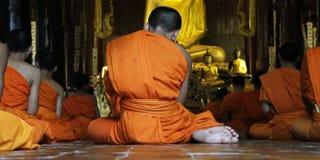 Monk praying. Detail of orange dress of monk during praying in buddhist temple Royalty Free Stock Images