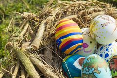 Detail of painted Easter eggs with different forms, cartoons and bright colors placed in a bird nest outdoors on a sunny day.  stock photos