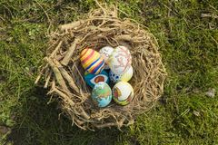Detail of painted Easter eggs with different forms, cartoons and bright colors placed in a bird nest outdoors on a sunny day.  royalty free stock photography