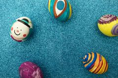 Detail of painted Easter eggs with different forms, cartoons and bright colors on a shiny blue background.  royalty free stock photography