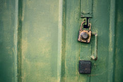 Detail of the painted metal door with old padlocks, closeup. Detail of the painted metal surface with old padlocks, background Royalty Free Stock Images