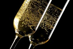 Detail of a pair of flutes of champagne with golden bubbles. On black background Royalty Free Stock Image