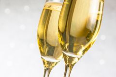 Detail of a pair of flutes of golden champagne on silver bokeh Stock Images
