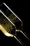 Detail of a pair of tilted flutes of champagne with golden bubbles Royalty Free Stock Photos