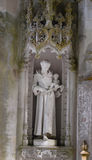 Detail in the park - old stone statue of monk with cross and baby, Quinta da Regaleira in Sintra, Portugal. Detail in the park - old stone statue of monk with Stock Images