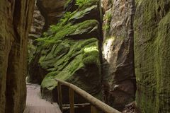 Bridge forming passage over beautiful chasm. Detail passage down in chasm gap among moss rocks Stock Photo