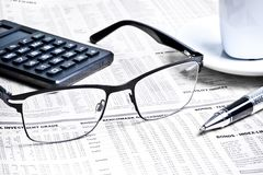 Detail of a pen and glasses near a calculator with cup of coffee Stock Photography