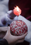 Detail penitent red holding a candle pouring wax on a ball that holds a child in the hand during Holy Week. Spain Royalty Free Stock Image