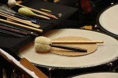 Timpani and different sizes of timpani mallets, drum brushes and maracas. royalty free stock images