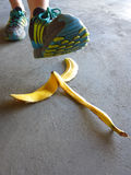 Detail of Person Stepping on Banana Peel and Slipping Royalty Free Stock Photo