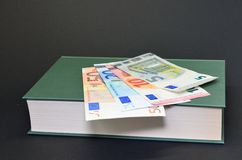 Detail photo of book with euro banknotes money on black background Royalty Free Stock Photography