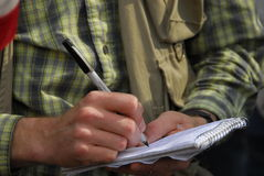 Detail photo of man journalist taking notes. Hand with pen writing on spiral notebook Royalty Free Stock Photos