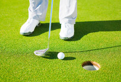 Detail Photograph of Man Putting Golf Ball into the Hole Stock Images