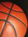 Detail photography of basketball ball. Detail photography of orange structured basketball ball on the black background Royalty Free Stock Photos