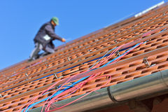 Detail of photovoltaic cables on the roof with worker in the background Stock Images