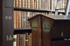 Shelf of old books in library. Detail picture of one of the bookshelves in the Long Room at Trinity College in Dublin, Ireland Stock Image