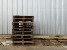 Pile of old wood pallet on dirty ground in front of steel wall in industry Royalty Free Stock Photography