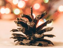 Detail of a pine cone and Christmas lights in background stock photography