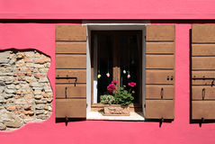 Detail of a pink facade with wooden window Royalty Free Stock Images