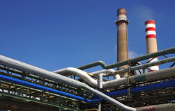 Detail of pipes in chemical factory. With two chimneys Royalty Free Stock Photo