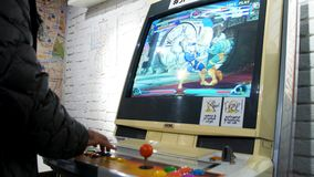 Detail of players hands interacting and playing with joysticks and buttons on an old arcade game in a gaming room Stock Photo