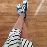 Detail with pleated striped skirt and sport shoes. Details with a woman s legs wearing a pleated striped navy skirt and dark blue Converse shoes Royalty Free Stock Image