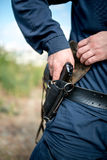 Detail of a police officer holding gun. Royalty Free Stock Image