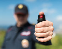Detail of a police officer holding pepper spray. Royalty Free Stock Photos