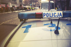 Detail of a police Policja car in Poland, demonstration in bac. Kground, vintage effect Royalty Free Stock Photo