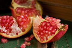 Detail of pomegranante seeds. Horizontal photo with single piece of pink pomegranate divided to three parts with few seeds spilled from fruit on green board. Few Royalty Free Stock Photos