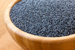 Detail of poppy seeds in wood bowl on wood surface. Royalty Free Stock Image