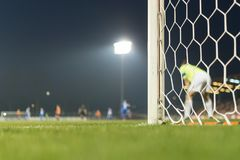 Detail of the post and net of the football goal. In the background players in action stock image