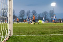 Detail of the post and net of the football goal. In the background players in action royalty free stock image