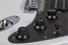 Detail of the potentiometers of a white electric guitar royalty free stock photo
