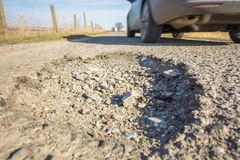 Dangerous hole in the asphalt surface of a highway with passing car stock photos