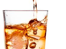 Detail of pouring scotch whiskey in glass with ice cubes on white. Detail of pouring scotch whiskey in glass with ice cubes isolated on white background Royalty Free Stock Photos