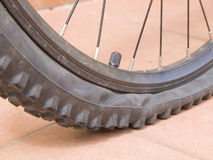 Detail punctured bicycle wheel 2. Closeup of a mountain bike wheel. The wheel is flat and has studs royalty free stock image