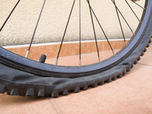 Detail punctured bicycle wheel. Closeup of a mountain bike wheel. The wheel is flat and has studs stock images