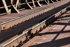 Detail of railway tracks on old metal bridge, sun casting shadow stock image