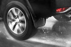 Detail of the rear wheel of a car driving in the rain stock image