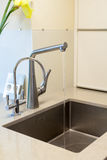 Detail of a rectangular designer kitchen sink with chrome water tap. Stock Image