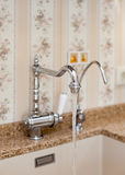Detail of a rectangular designer kitchen sink with chrome water tap. Stock Images