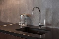 Detail of a rectangular designer kitchen sink with chrome water tap against a gray textured wall. Detail of a rectangular designer kitchen sink with chrome stock photos