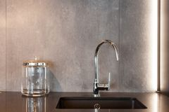 Detail of a rectangular designer kitchen sink with chrome water tap against a gray textured wall. Detail of a rectangular designer kitchen sink with chrome stock photo