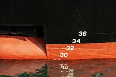 Ship Prow with Anchor and Waterline. Detail of a red and black ship prow with a waterline water level measurement and anchor stock photo