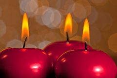 Detail of red christmas candles on golden bokeh background Royalty Free Stock Photo
