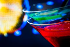Detail of red cocktail with golden sparkling disco ball background with space for text Stock Photo