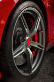 Detail on red super sport car wheel with red center and red breaks. And metal rims Stock Photography