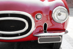 Detail of a red vintage car. Close-up of front of a red vintage car Royalty Free Stock Photos
